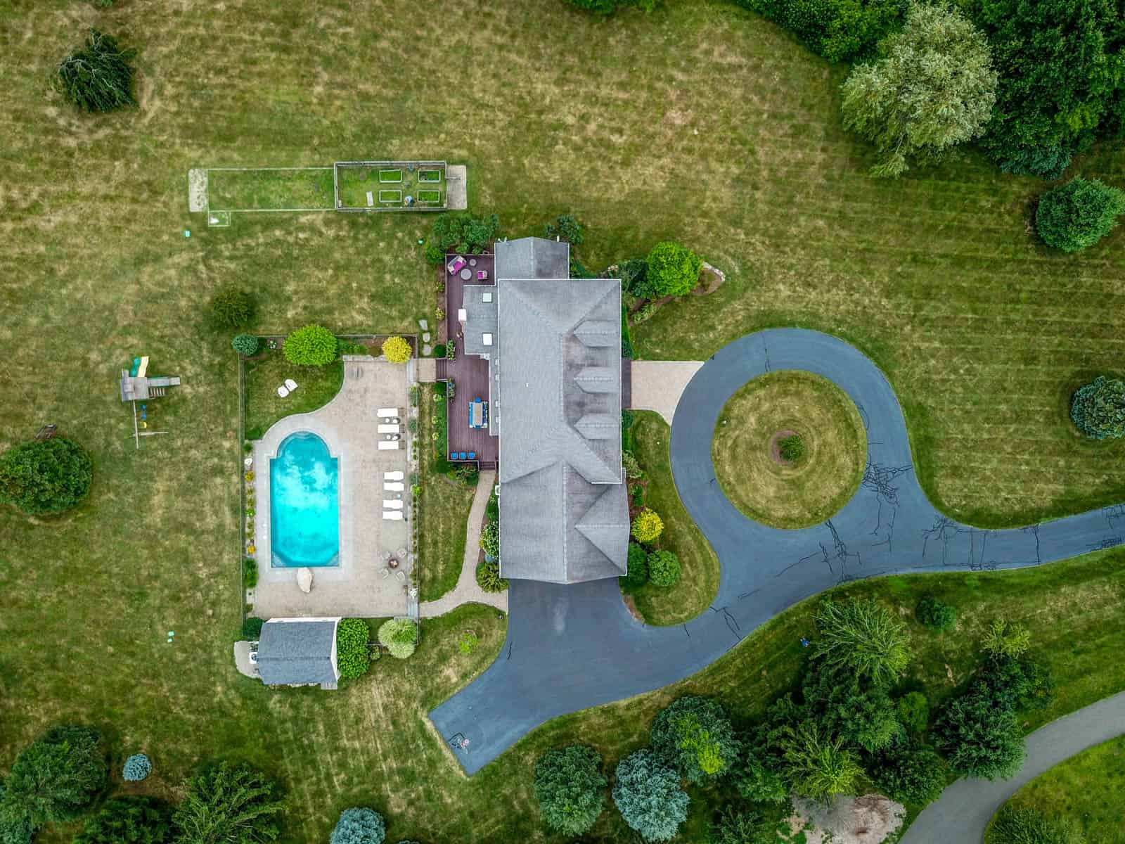 looking down at Connecticut home with mown lawn, circular driveway, and swimming pool in backyard with fire pit