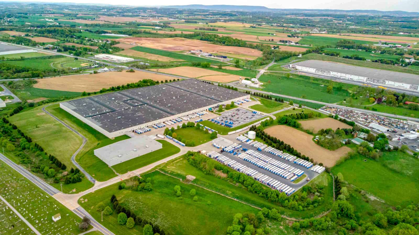 drone photo of shipping warehouse in Pennsylvania with lots of trucks and truck beds