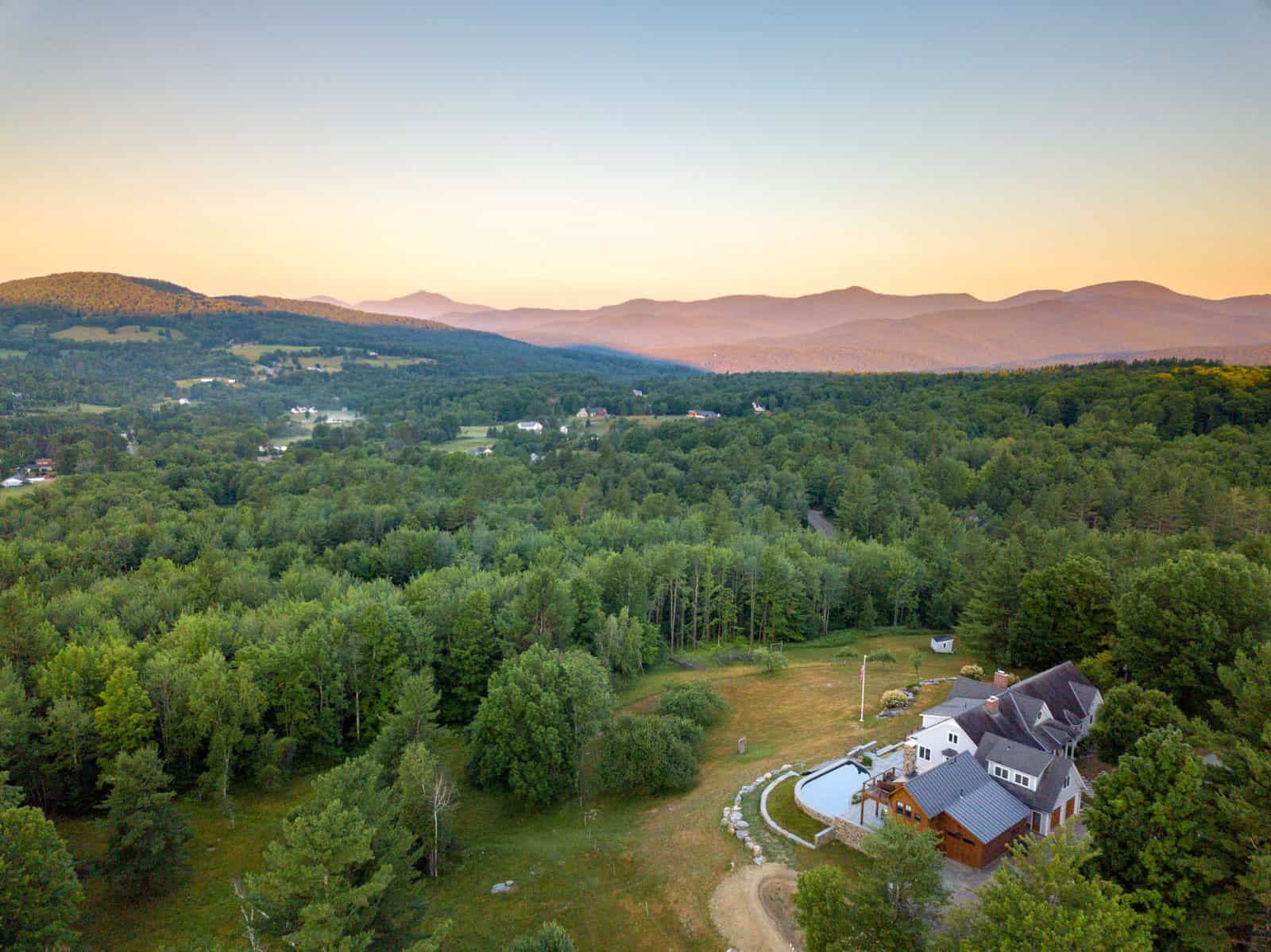 house in Stowe, VT aerial drone photo during sunrise with mountains in background