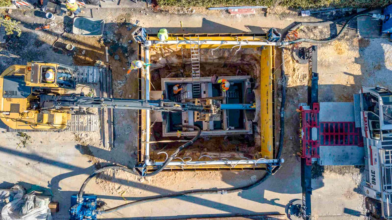 aerial view looking down at construction site where 6 workers in yellow vests are installing a new water pipe in Florida