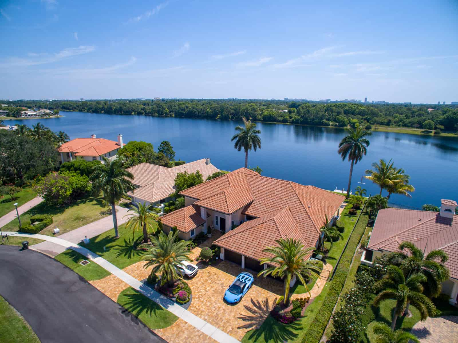 house in Boca Raton, FL, with lake in background and two Ferrari's parked in the driveway