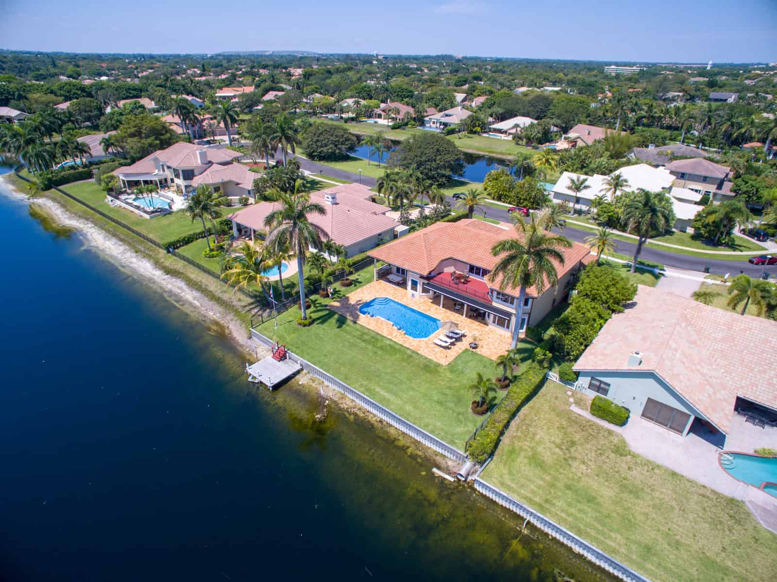 home in Florida next to lake with swimming pool in backyard and palm trees