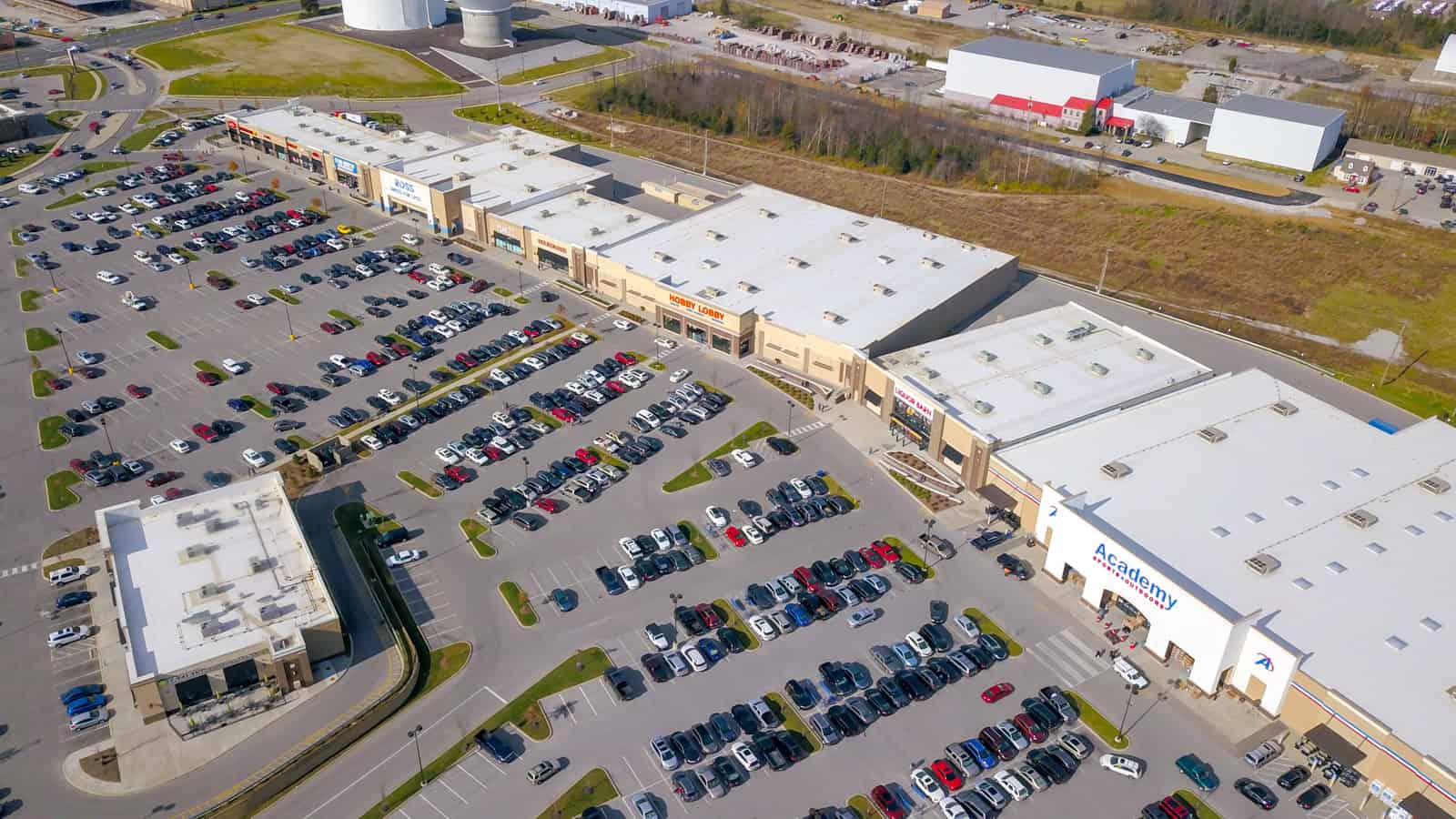 aerial drone photo of commercial real estate shopping plaza filled with cars in the parking lot