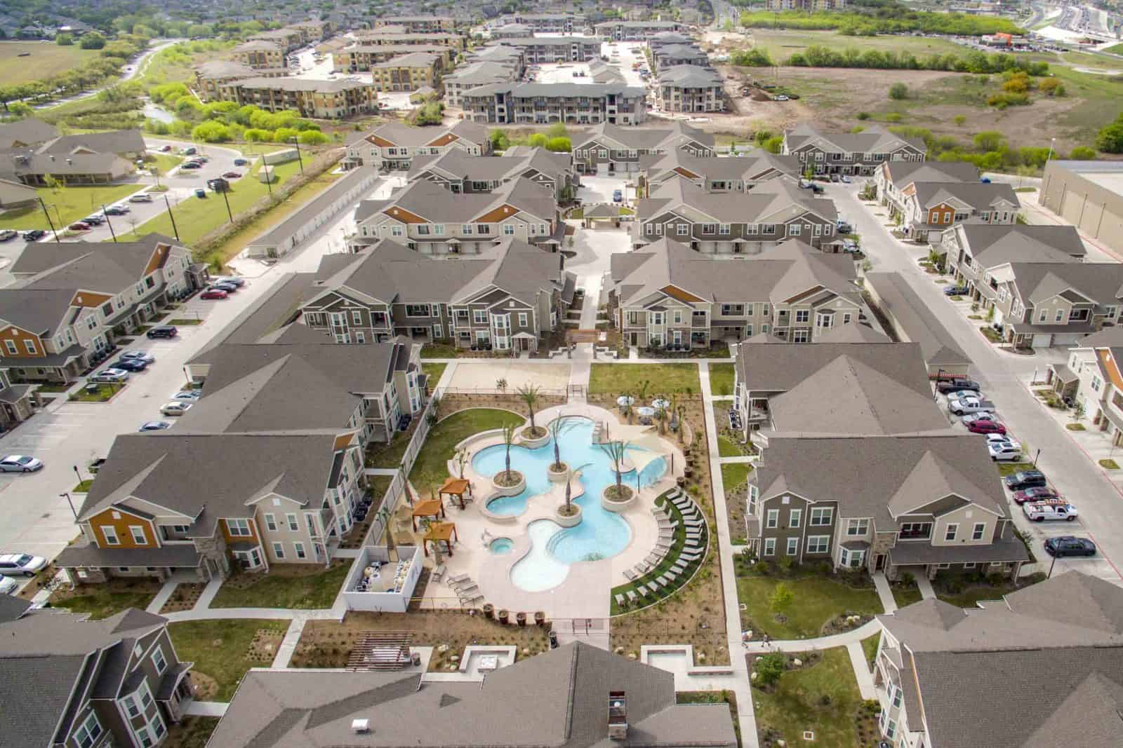 drone photo of apartment complex with swimming pool in center