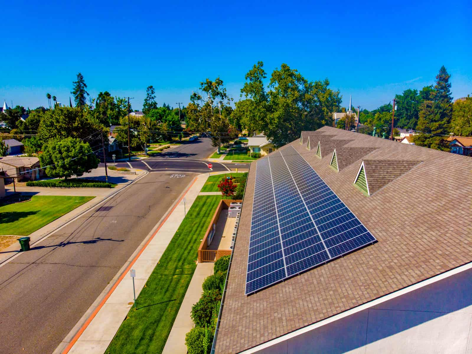 aerial drone photo of large solar panel array installed on rooftop of building in California