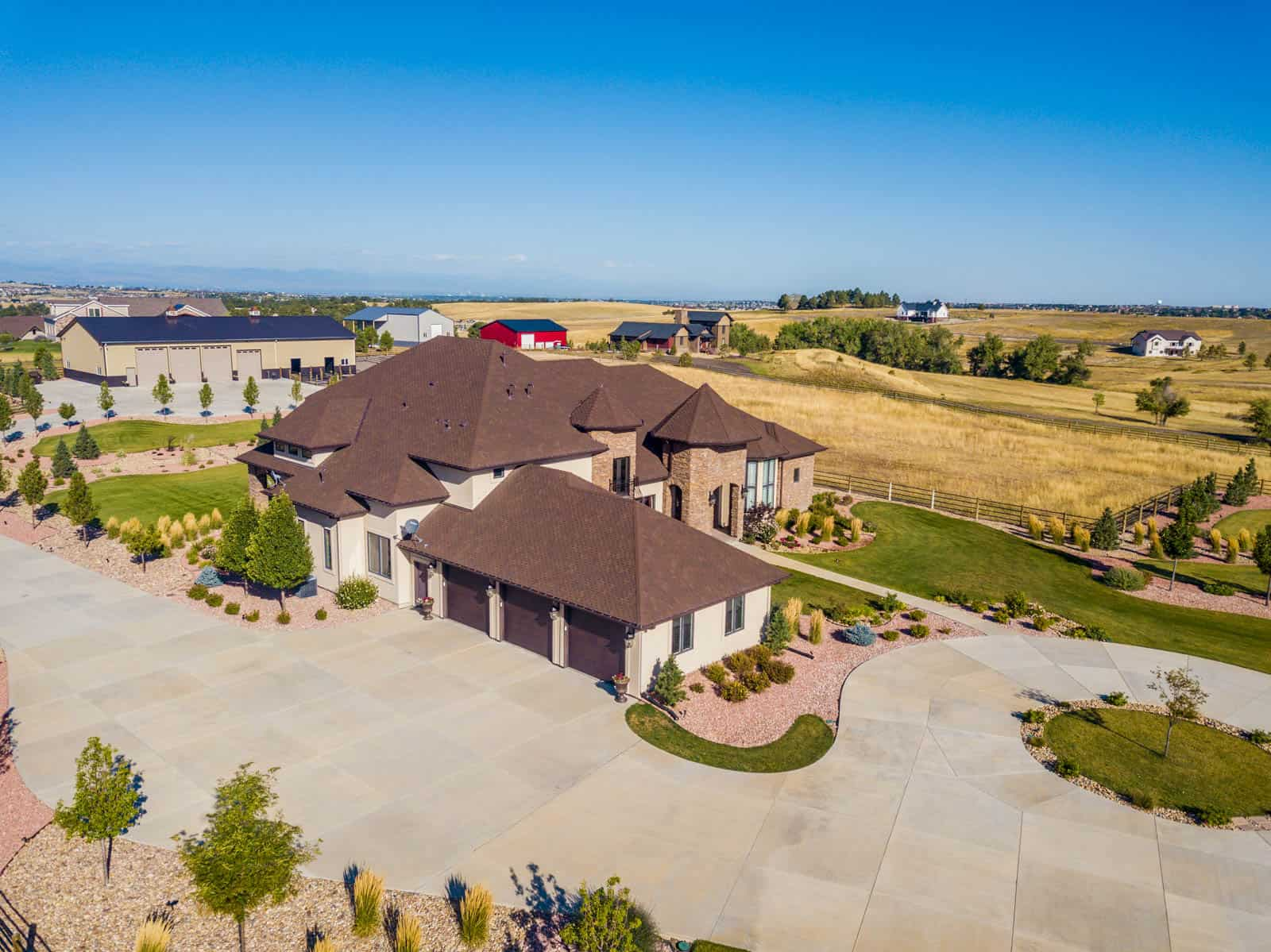side angle drone photo of residential property with three car garage in Parker, Colorado