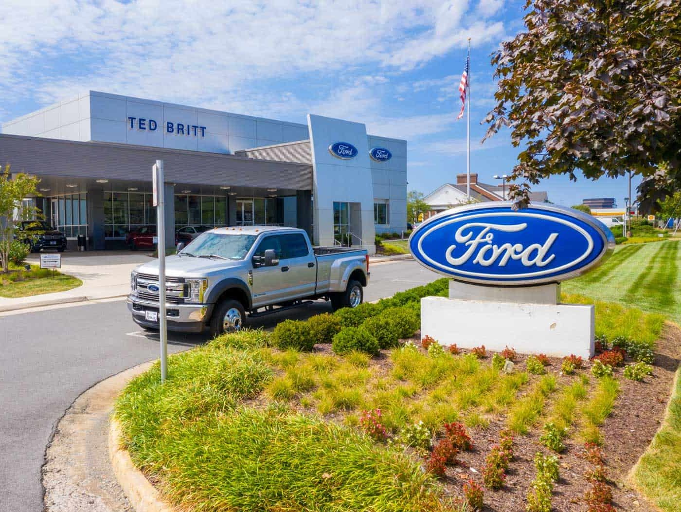 low altitude drone photo of front of Ford dealership with F150 truck parked in front in Fairfax, VA