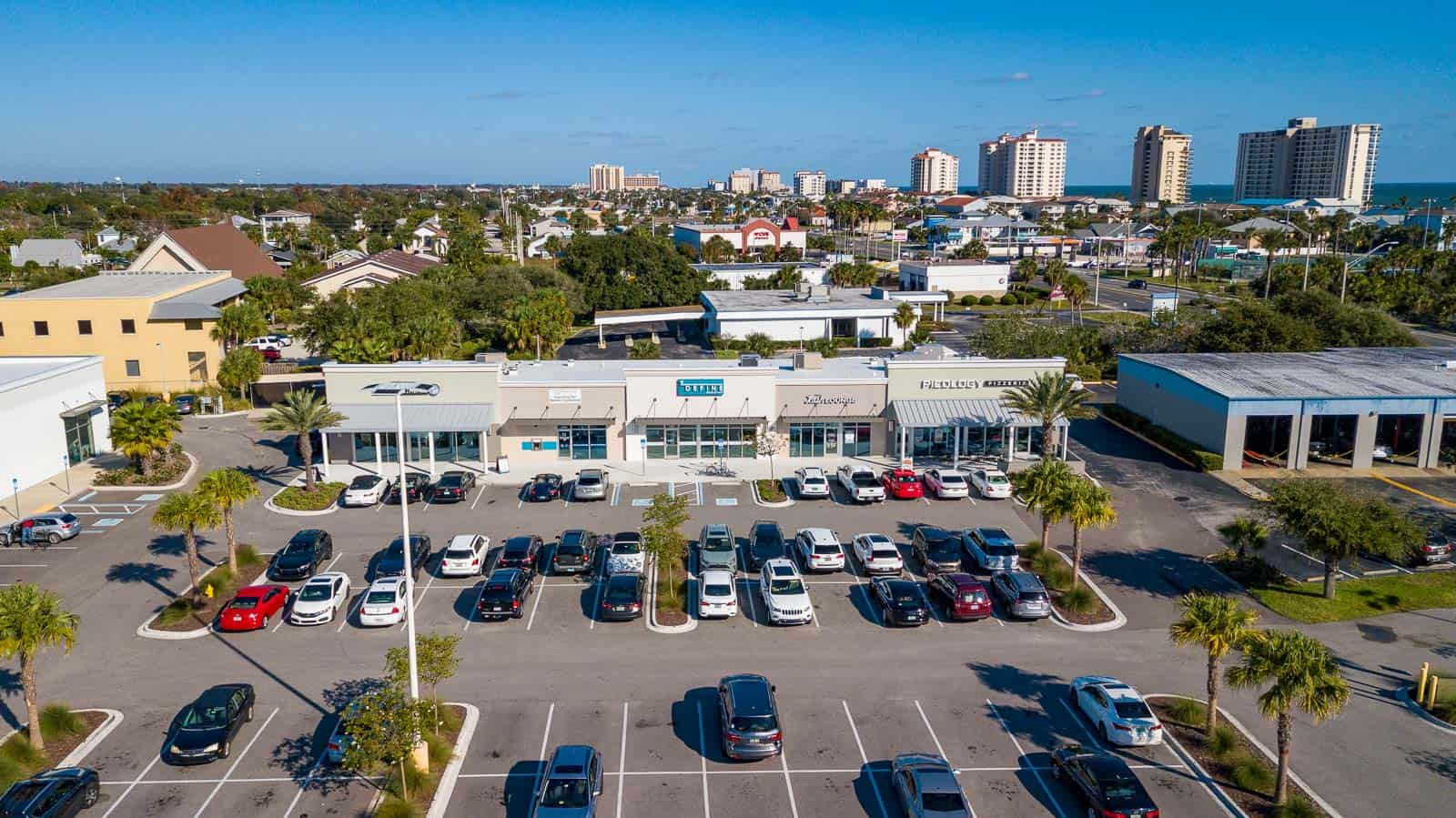 low altitude drone photo of store in commercial shopping plaza in Jacksonville Beach, FL