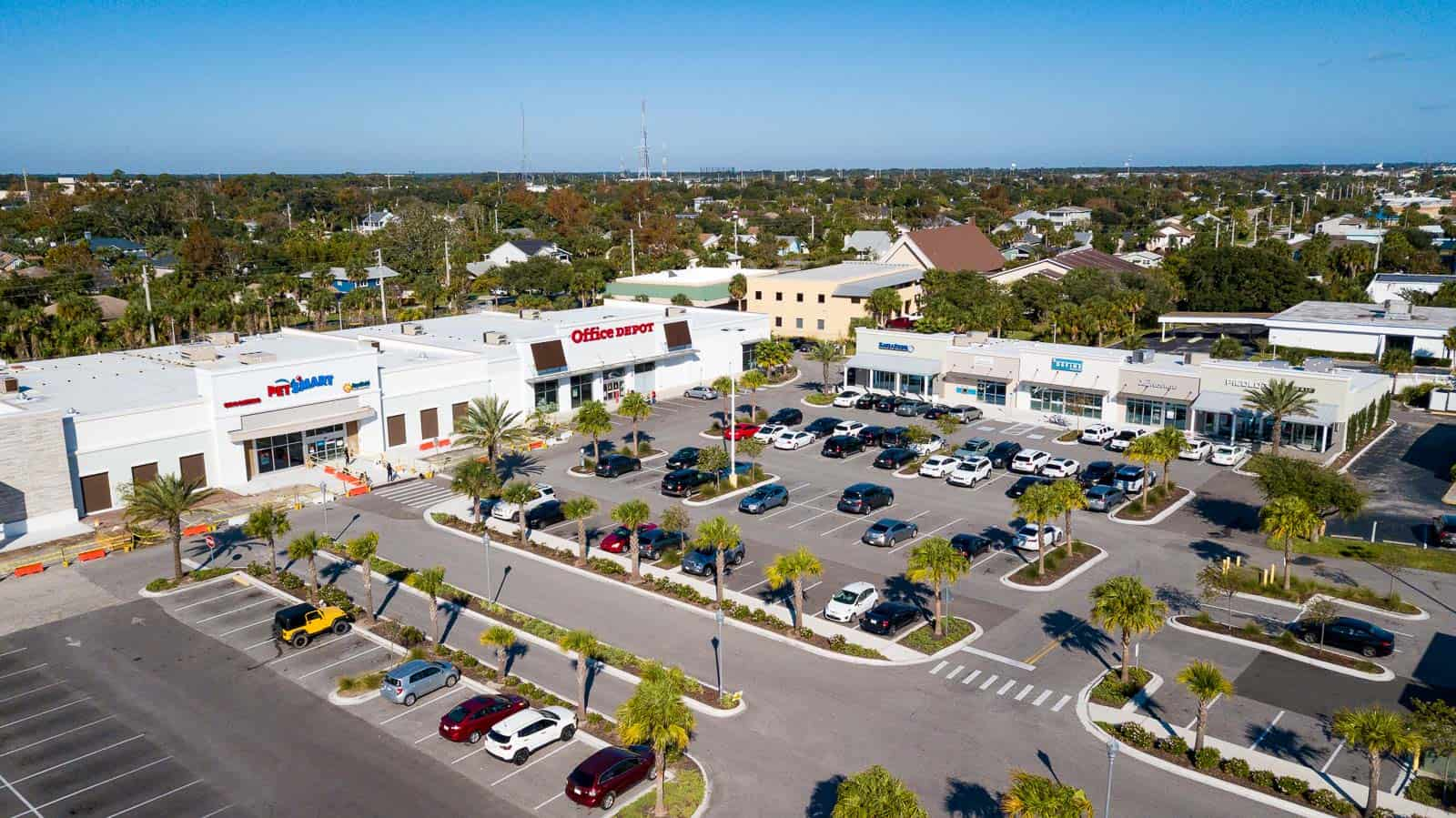 drone photo of commercial shopping plaza parking lot and storefronts in Jacksonville Beach, FL